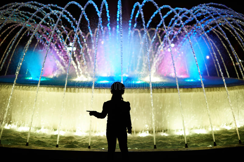 Small kid play with colorful fountain royalty free stock images