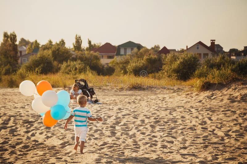 Small kid is playing with colourful balloons at the beach, happy lifestyle family concept.  stock photography