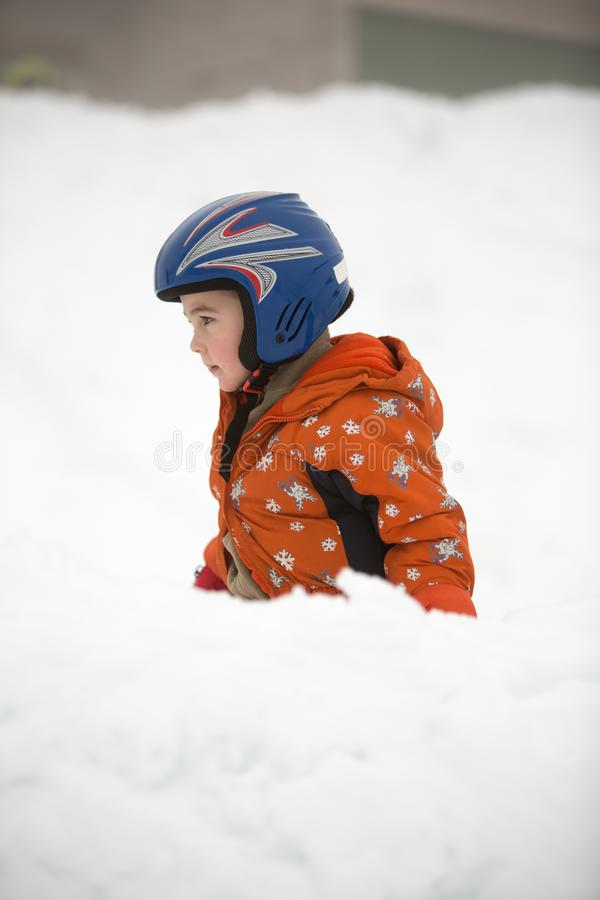 Young little boy in orange overall and blue helmet plays outdoor at winter time. royalty free stock photo
