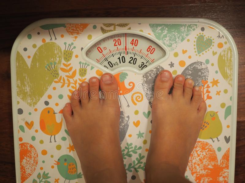 Small kid`s legs standing on the scales closeup. top view royalty free stock photo