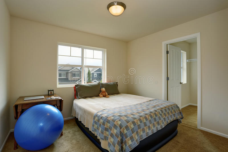 Small kids bedroom with table, blue ball and small green bed royalty free stock images