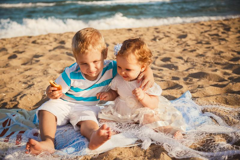 Small kids are playing and having fun at beach together near the ocean, happy lifestyle family concept.  royalty free stock photo