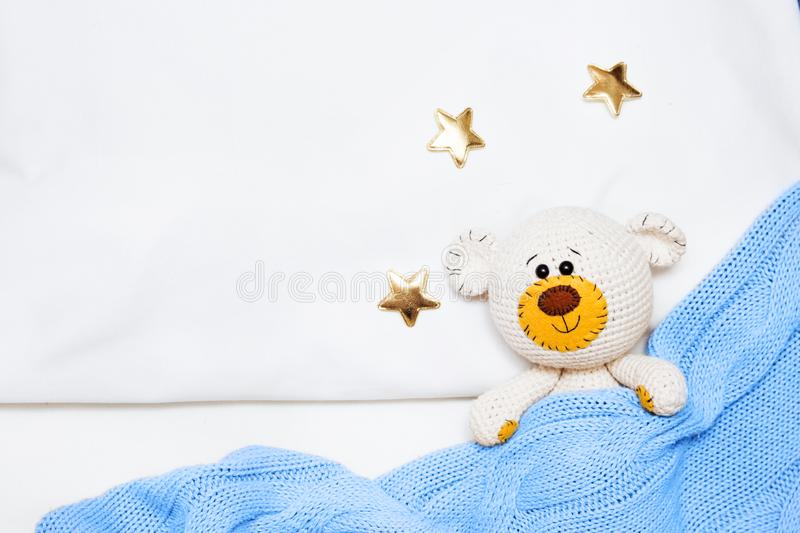 A small knitted amigurumi baby toy-bear is covered with a blue blanket, flat lay, top view stock photography