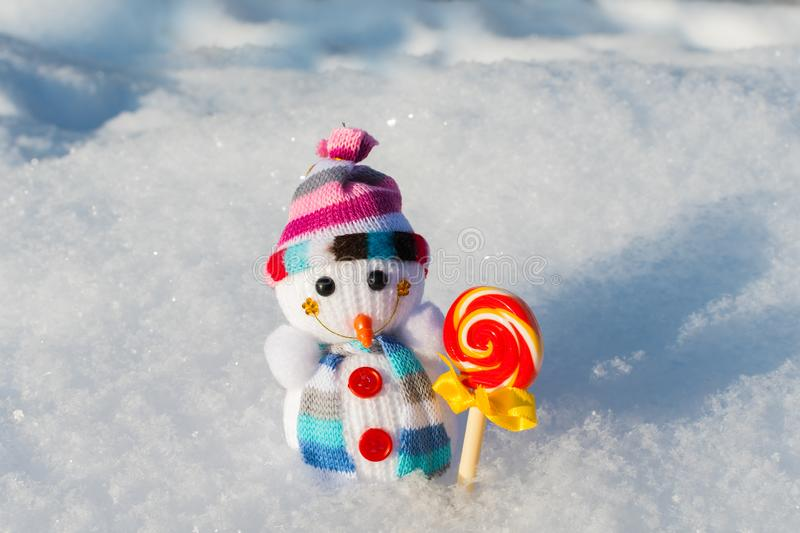 Small knitted snowman with candy in the snow royalty free stock photography