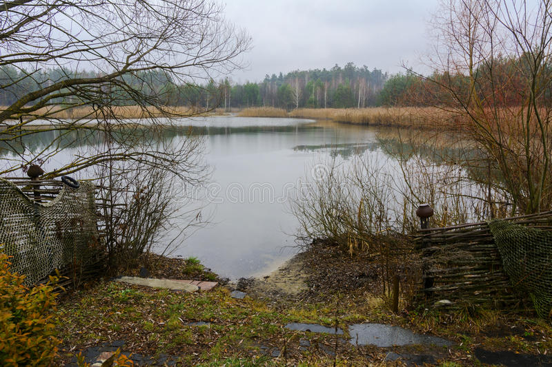 A small lake near the wooden house stock photography