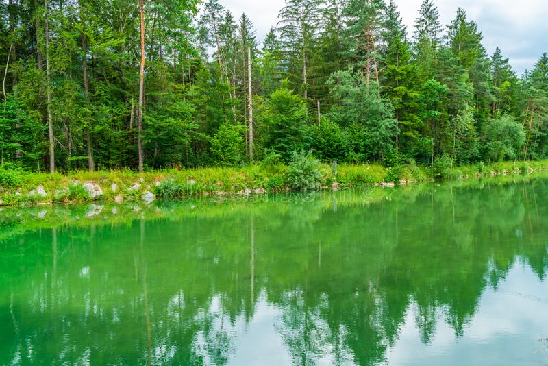 A small lake with reflections of trees in the water, Austria stock photography