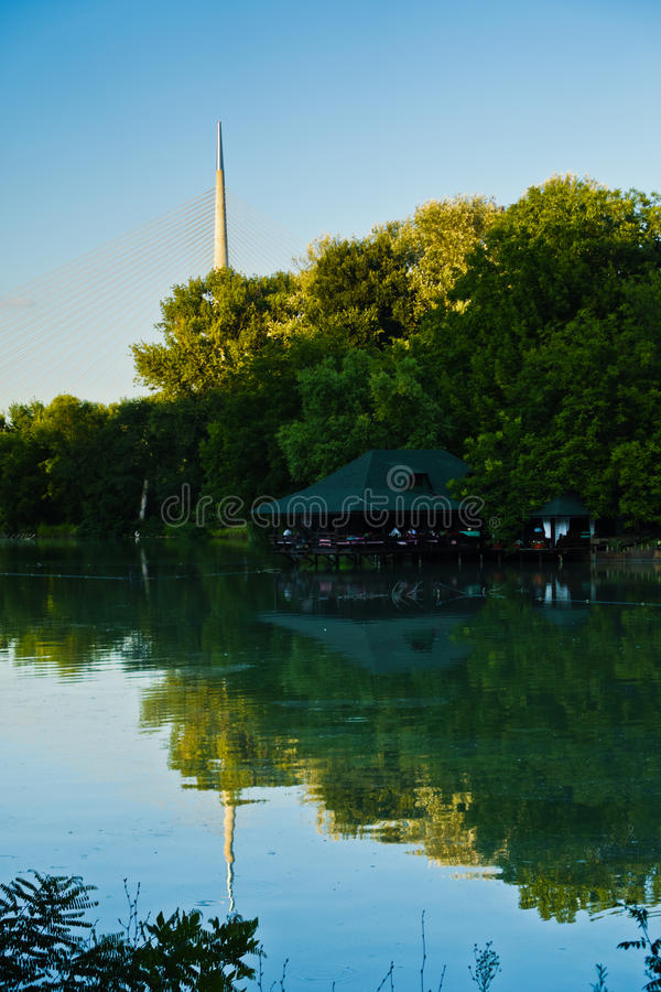 Small lake with a wooden cabin, Ada cable bridge in a background, Belgrade. Serbia royalty free stock photo