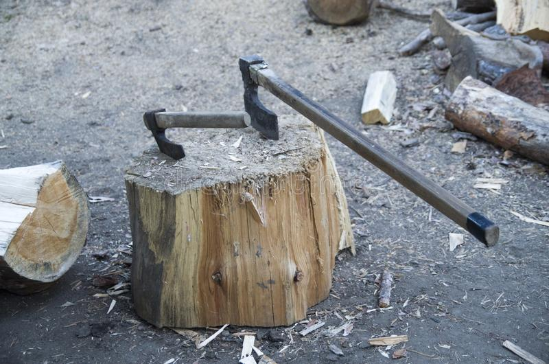 Small and large axes stuck in stump. Small and large axes stuck in a stump stock image