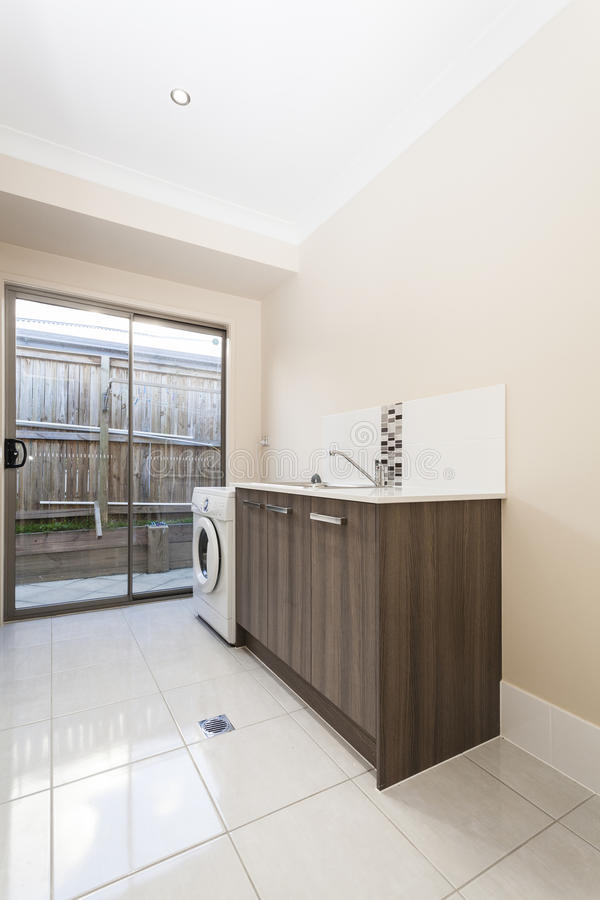Small laundry. Tiled laundry room with sink and washing machine royalty free stock images