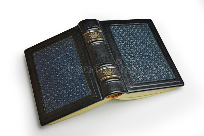 Small leather book with patterned surface lay down to the table isolated.  stock image