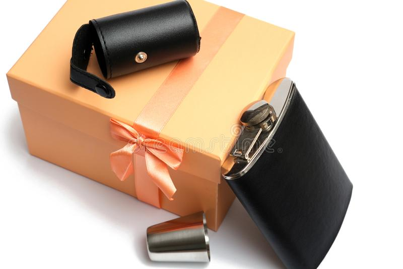 Small leather hip flask with metal mug at orange giftbox. On a white background stock photos