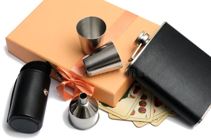 Small leather hip flask with metal mugs and pocket and funnel at orange giftbox. A white background royalty free stock photo