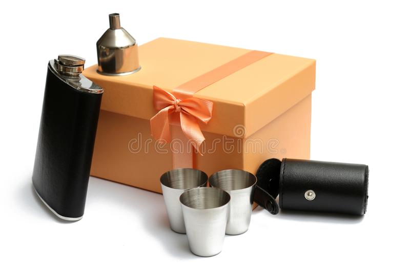 Small leather hip flask with three metal mugs and funnel at orange giftbox. On a white background royalty free stock photography