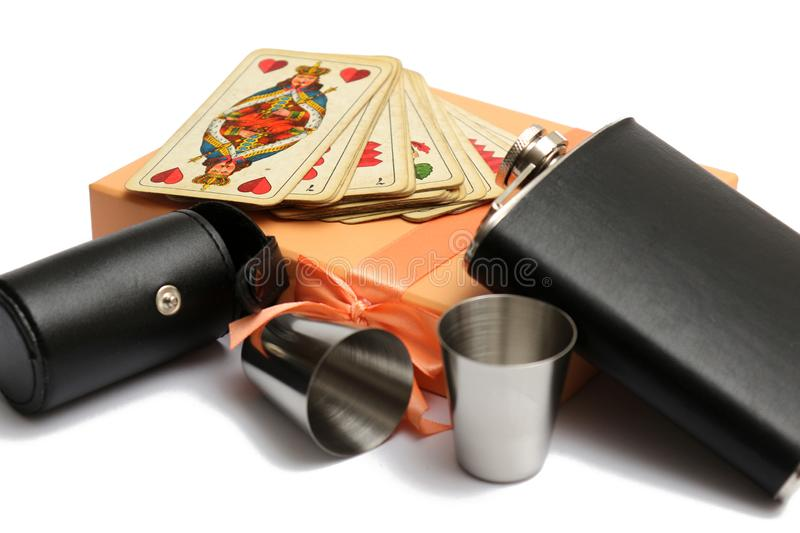 Small leather hip flask with two metal mug and old plauying cards at orange giftbox. On a white background stock image