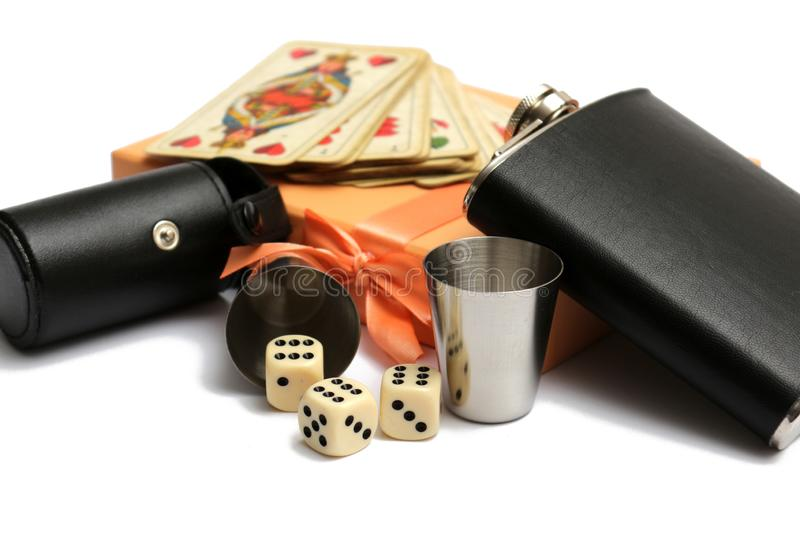 Small leather hip flask with two metal mugs and three cubes and old playing cards at orange giftbox. A white background stock images