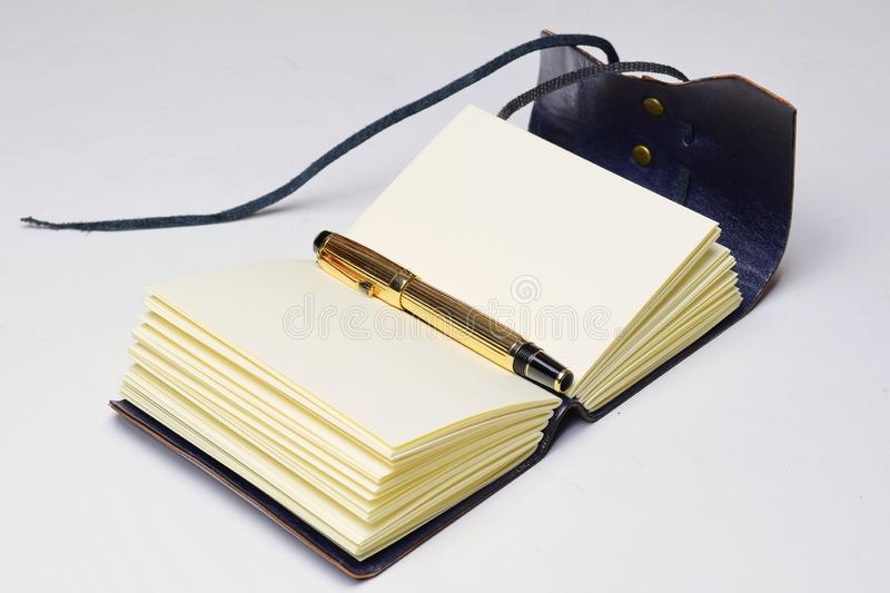 Small leather journal opened on the half and with the gold pen between pages. Lay down to the table stock photography