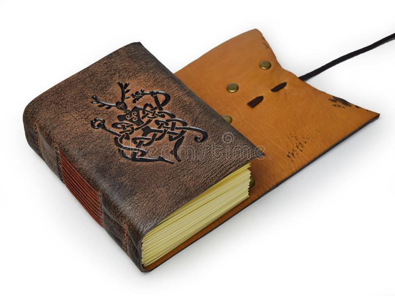 Small leather journal with two different leather colors lay down to the table. With embossed symbol of the Cernunnos - ancient viking symbol of underworld royalty free stock photos