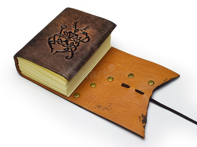 Small leather journal with two different leather colors lay down to the table. With embossed symbol of the Cernunnos - ancient viking symbol of underworld royalty free stock image