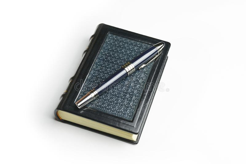 Small leather notebook with the pen over the patterned cover.  stock image