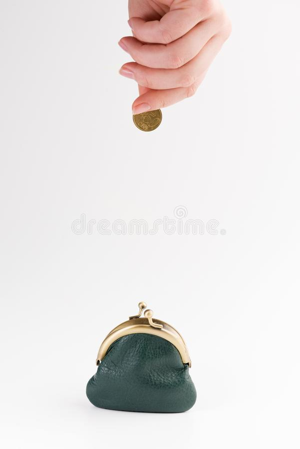 Small leather wallet and hand with gold coin isolated on white. Background royalty free stock photography