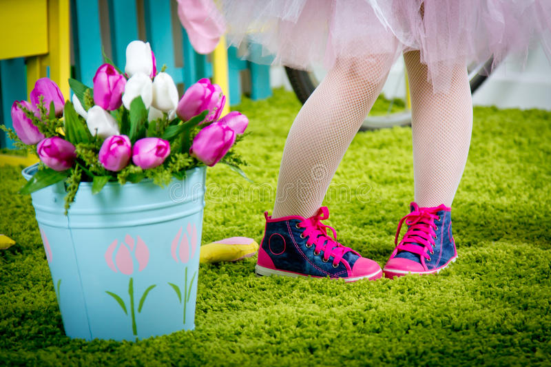 Small legs of the little girl in pink gym shoes. On the green carpet royalty free stock image