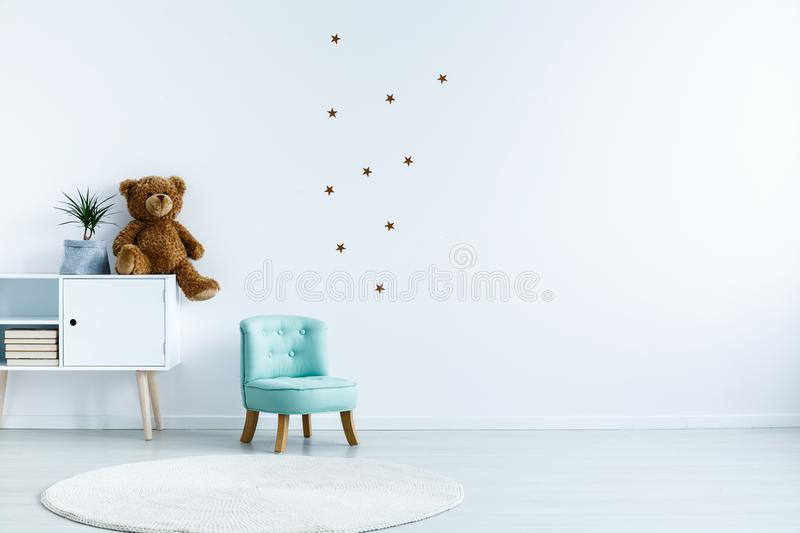 Small light blue armchair for kid standing in white room interior with stars on the wall, white rug and cupboard with royalty free stock images