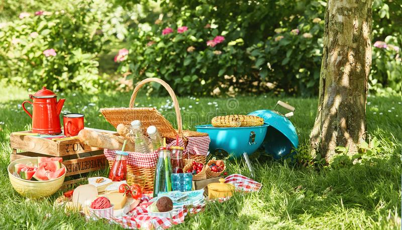Small grill and tree trunk next to picnic blanket stock images