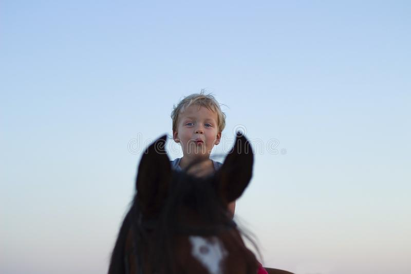 Small little boy riding his horse in sunset light. Cute toddler enjoys riding. Copy space stock photos