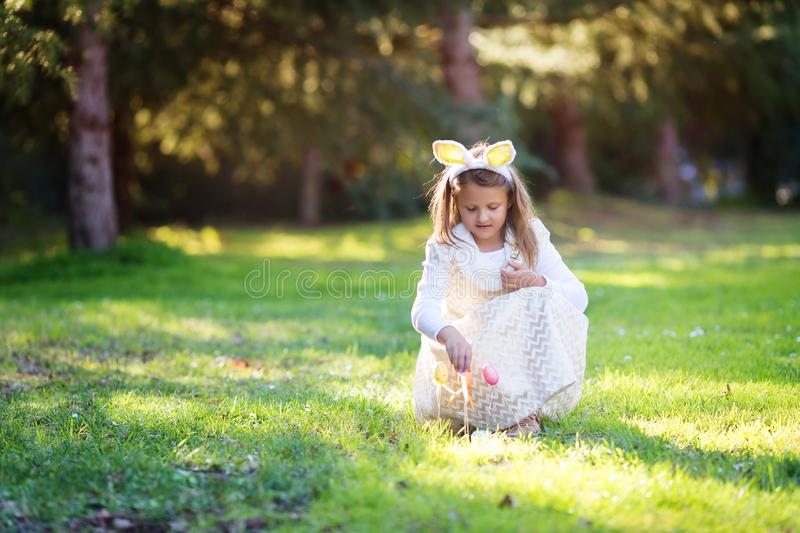 Small little Caucasian girl with Easter bunny ears, s playing with Easter egg pop sticks stock photography
