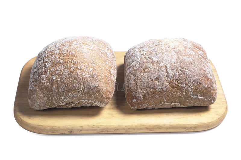 Loaves of bread ciabatta. Small loaves of bread ciabatta on wooden cutting board on white background stock images