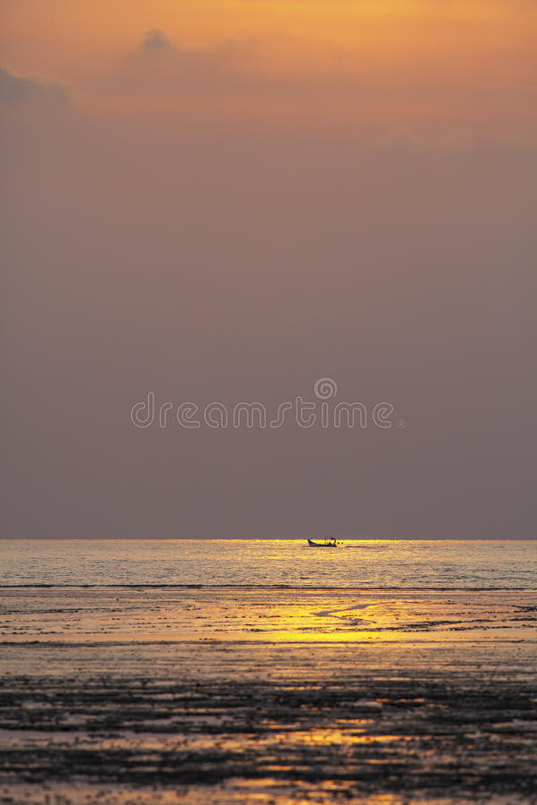 Small lone boat in the middle of sea when sunset. A shot taken when sunset, the small fishing boat still working in the middle of sea while the golden color stock image