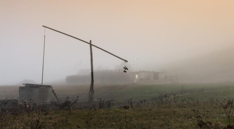Small lonely provincial farm with weel pole weel on a foggy morning near Sic village, Transylvania, Romania.  royalty free stock photos