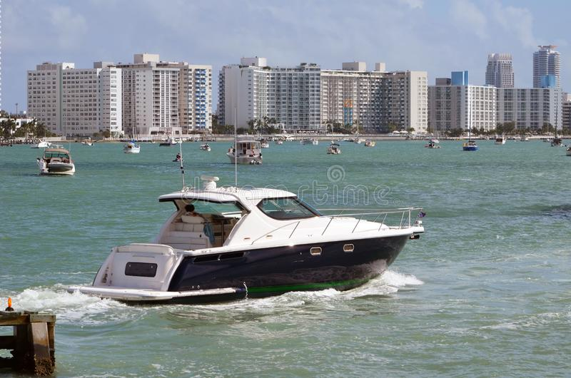 Motor Yacht and Southbeach Skyline. A small luxury motor yacht cruising on the intra-coastal waterway off Miami Beach,Florida with Miami Beach condo skyline in royalty free stock image