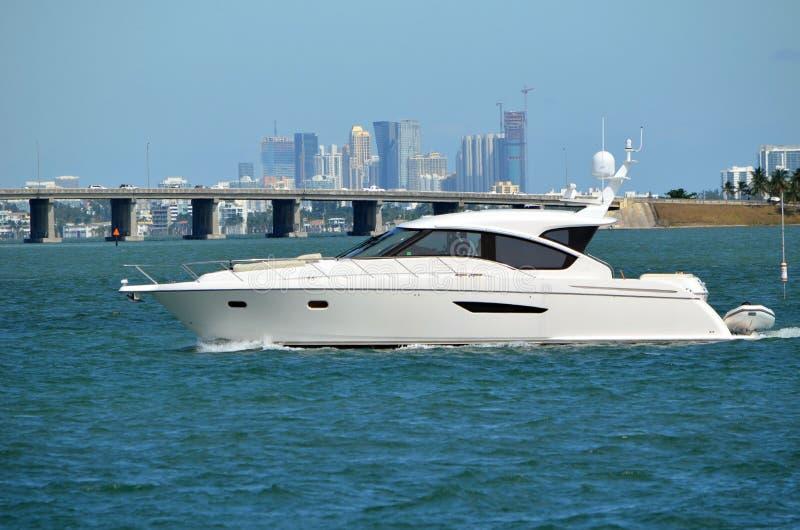 Small Luxury White Motor won the Florida Intra-Coastal Waterway. A white motor yacht on the Florida Intra-Coastal Waterway against a background of a causeway royalty free stock photos