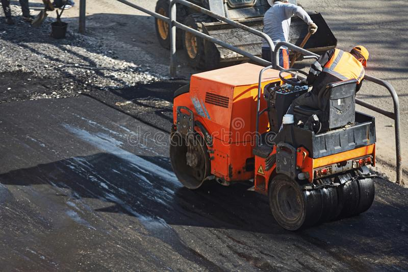 A small machine for laying a new asphalt. Asphalt paving. A small orange light machine for laying a new asphalt. Asphalt paving royalty free stock photography