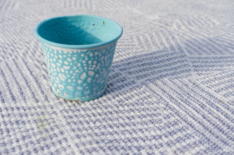Small macro close up of a single blue table decoration cup. On striped table carpet patern royalty free stock photography