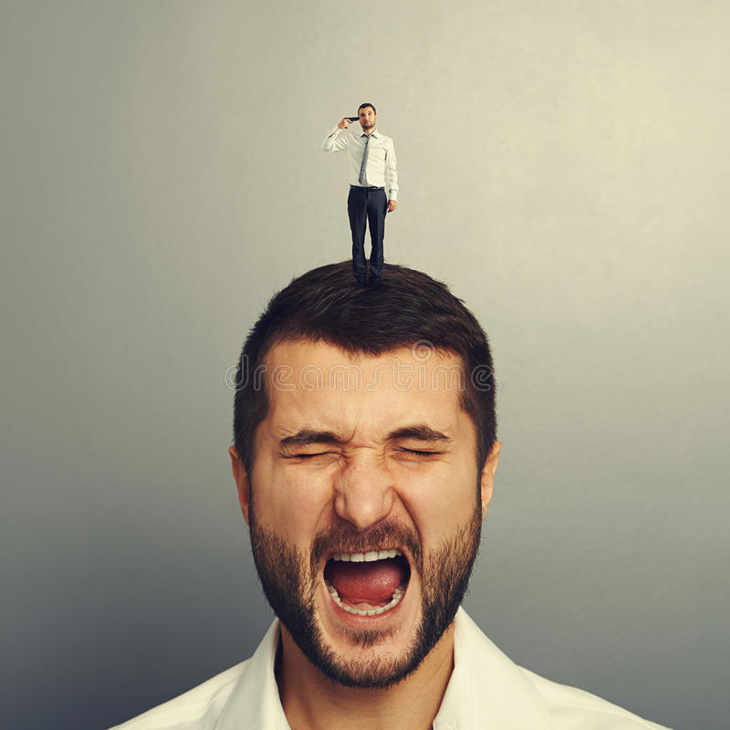 Small man with gun holding on the head. Of stressed man royalty free stock photography