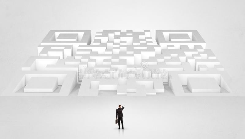Small man standing in front of a huge maze stock image