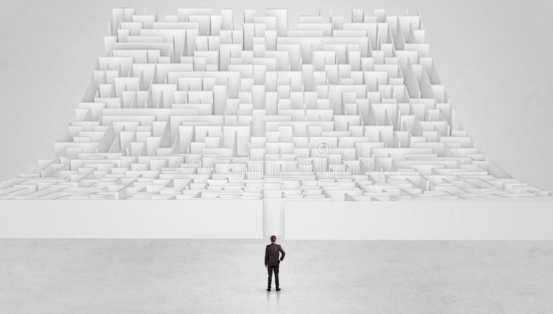 Small man standing in front of an infinity maze stock photography