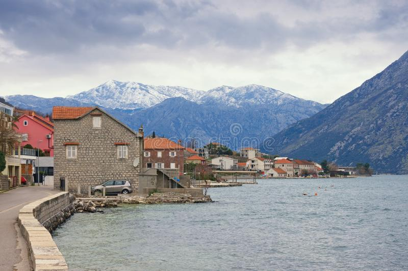 Small Mediterranean town near snow-capped mountains on cloudy day. Montenegro, Bay of Kotor, Prcanj stock image