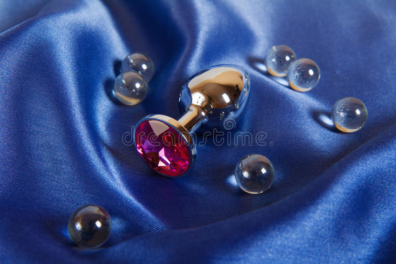 Small metal pink anal plug on blue. Small steel anal plug with pink crystal on blue satin background royalty free stock photo