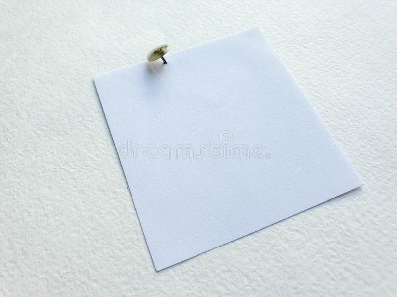 Small metal silver pushpin on white paper background stock images