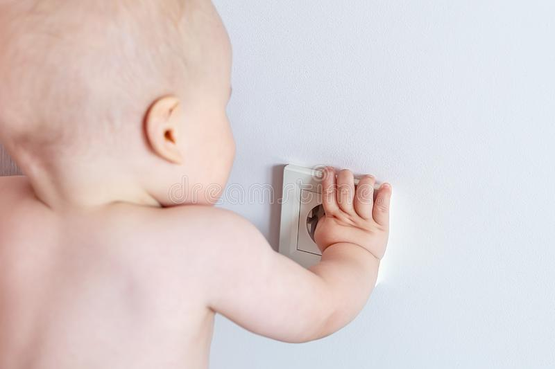 Small mischevious toddler boy playing and trying to put fingers in power electric socket in white wall at house. Child safety and. Protection. Happy childhood stock photos