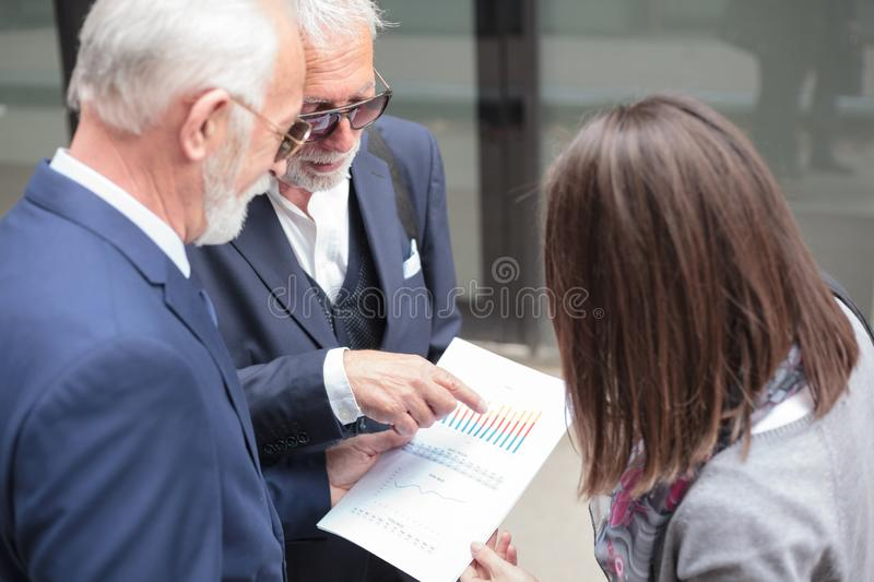 Small mixed group of business people having a meeting, discussing sales reports. Two senior gray haired businessmen and young women having a meeting in front of stock image