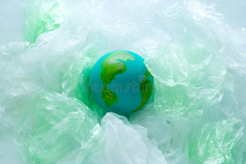small model of the  Earth planet among plastic bags, environment, global pollution  concept, earth day stock photo