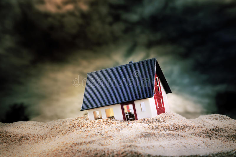 Small model of house in sand. Small model of house built on pile of sand stock photos