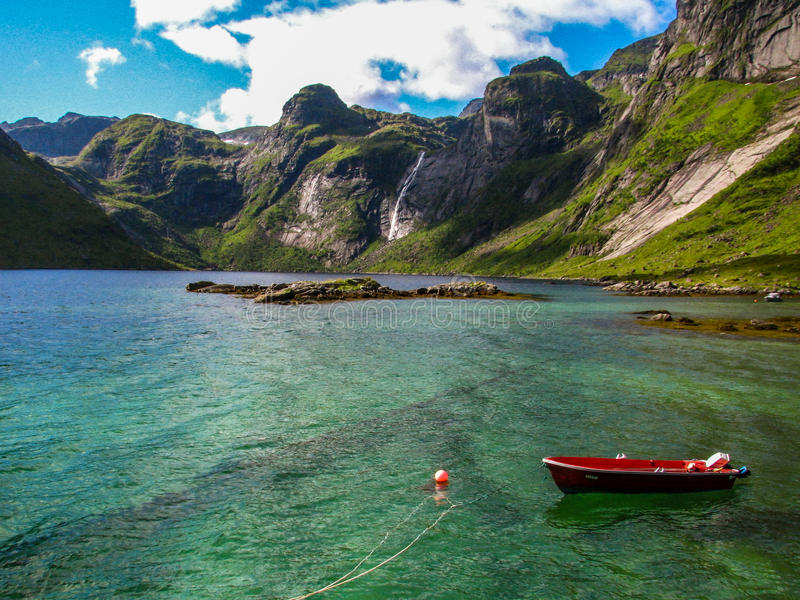 A small motor boat docked in the sea near the mountains in Lofoten, Norway stock photos