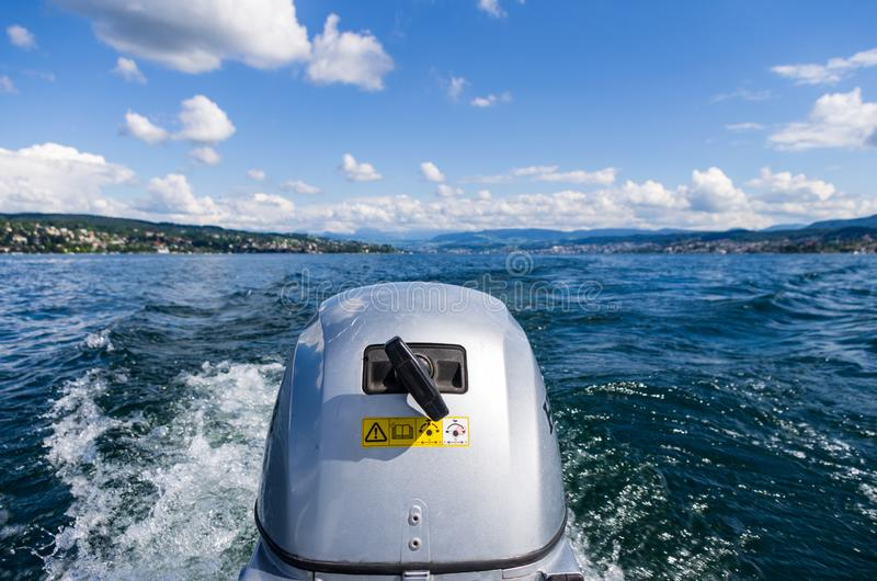 Small motor boat engine close up at full speed on lake Zurich sunny day. With puffy clouds royalty free stock photo