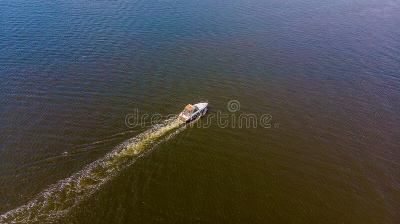 Small motor boat sailing fast captured from above. With a drone stock photography