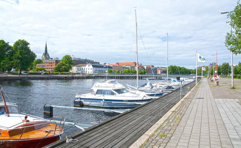 Small motorboats Nissan river Halmstad Sweden. HALMSTAD, SWEDEN - JUNE 7, 2015: Small motorboats moored along the quay by Nissan river with castle behind stock image